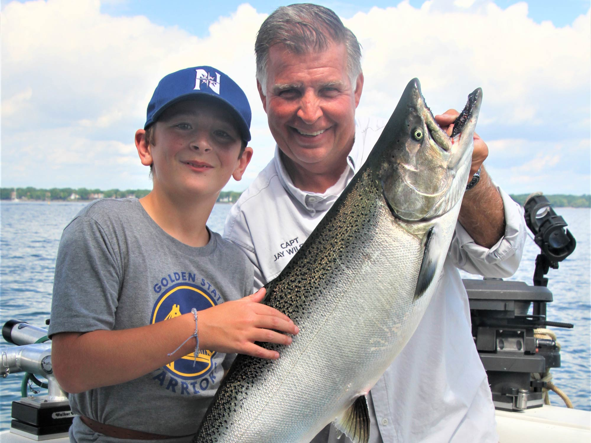 Grandfather and grandson holding a big Chinook Salmon with water and blue skies in the background