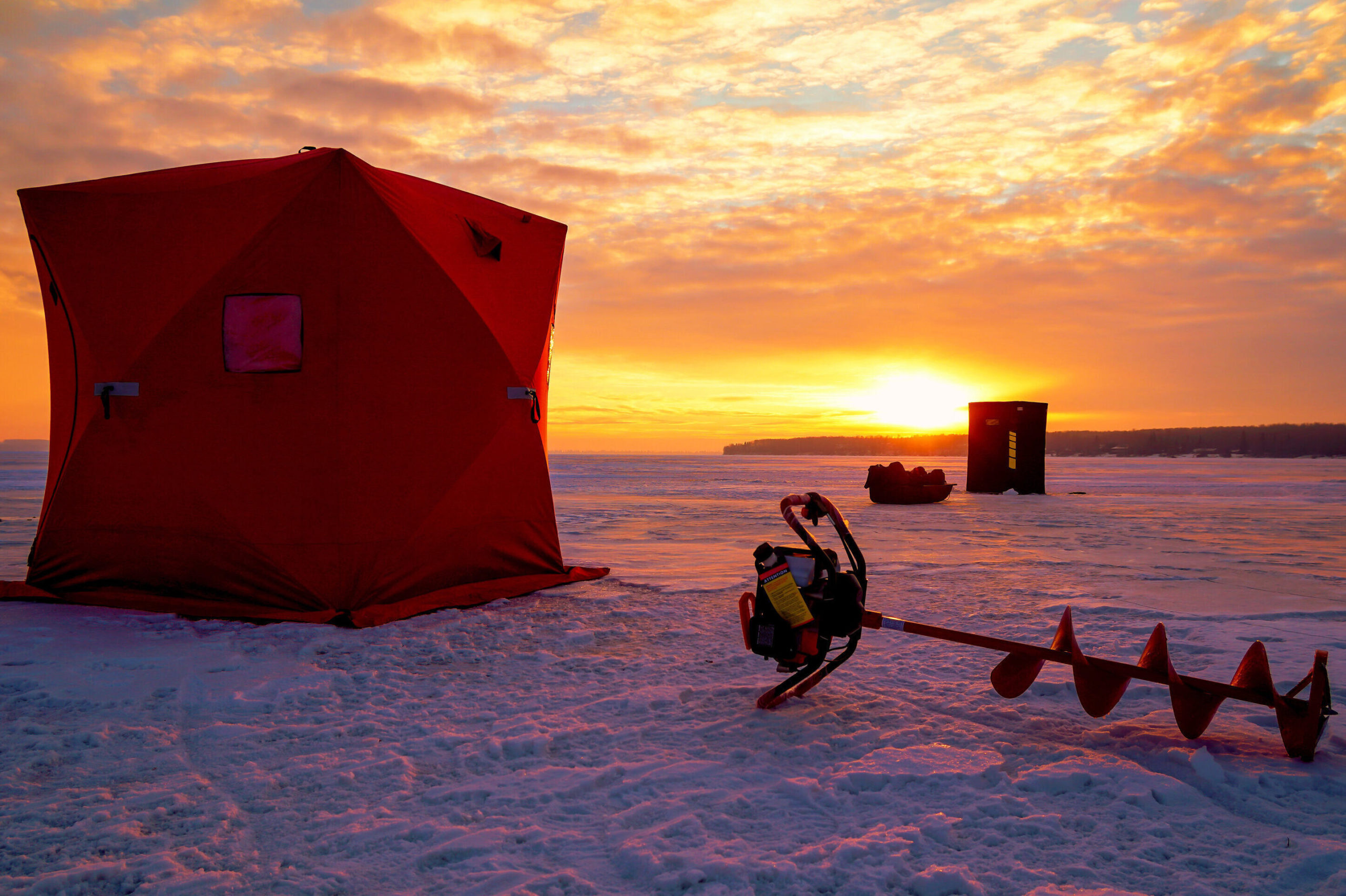 A tent and an ice drill on a frozen lake