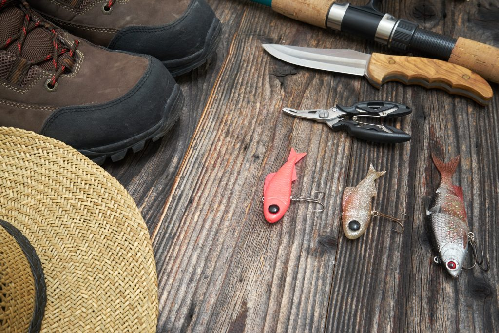 A selection of fishing equipment: a knife, pliers, lures, boots, fishing rod, and hat, all laid out on a wooden floor.