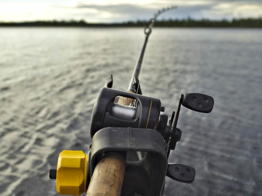 A trolling rod in its holder with the line in the water, water and shoreline in the background