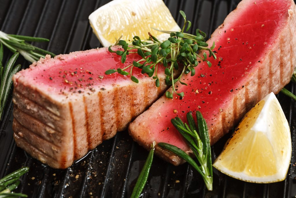 two Tuna steaks grilled rare with lemon on the side