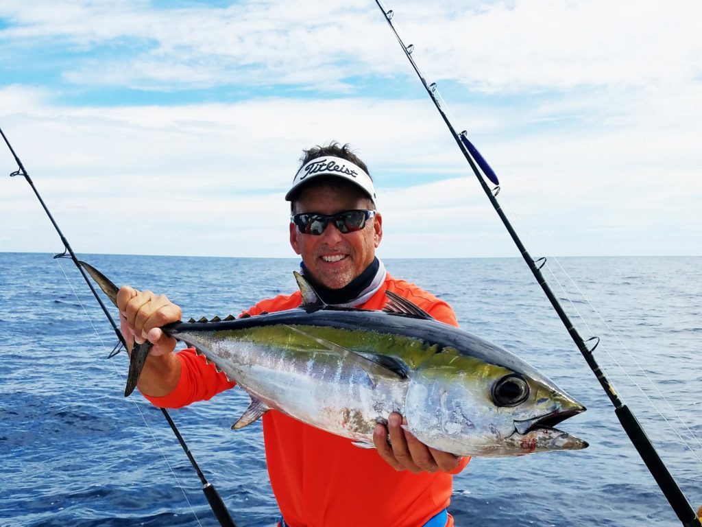 A smiling middle-aged angler standing on a boat, holding a Blackfin Tuna