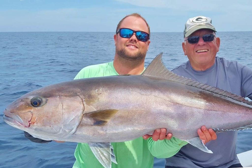 Two men hold a large Amberjack aboard a boat, with the ocean behind them