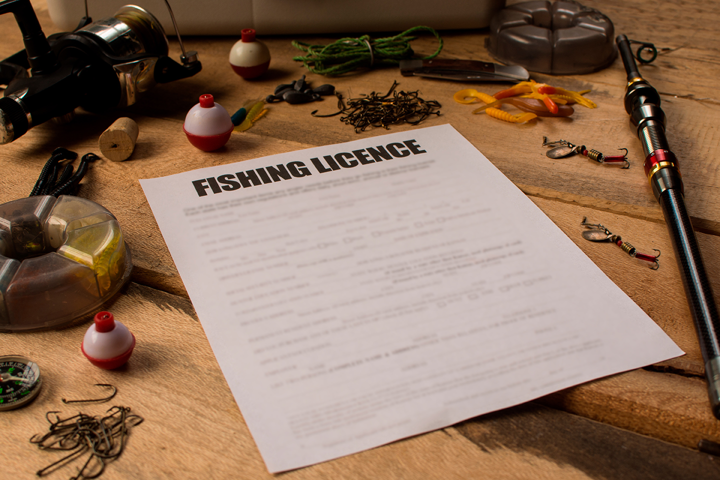 An example rod licence form on a table with an assortment of fishing equipment