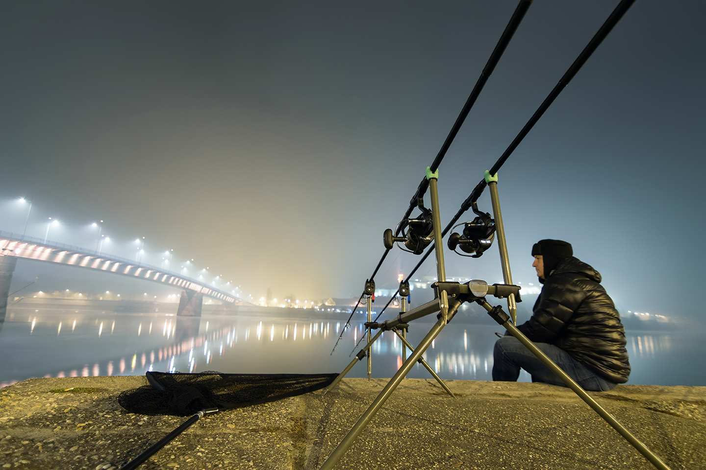 An urban angler fishing in London at night, with two fishing rods set up in the foreground and the lights of a bridge in the distance