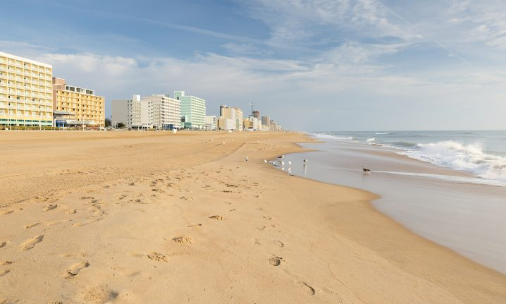 A yellow sandy beach with buildings in the left distance and sea on the right