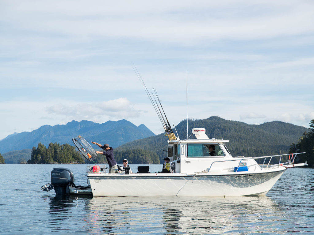 A charter boat in Vancouver Island, one of North America's greatest fisheries, with one angler throwing a crab pot into the water