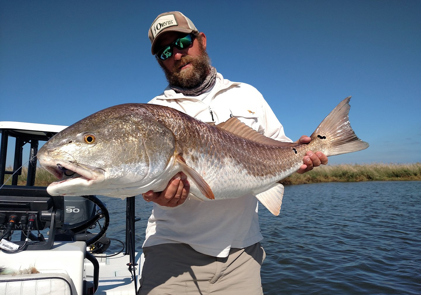 An angler on a flats fishing boat holding a large Bull Redfish with water and sky behind him.
