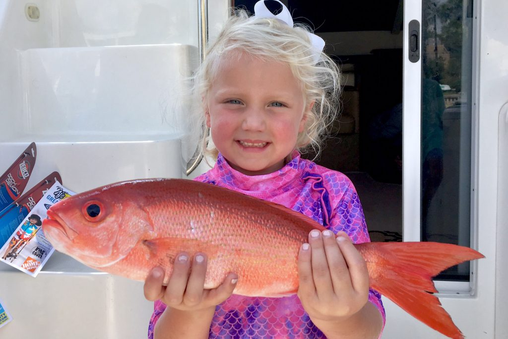 A small blonde child holding a Vermilion Snapper on a charter boat