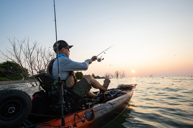 A man kayak fishing at sunset