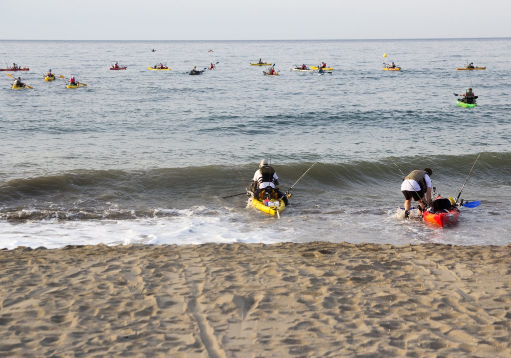 Two kayak anglers launching into the sea, with more fishing kayaks in the water ahead of them