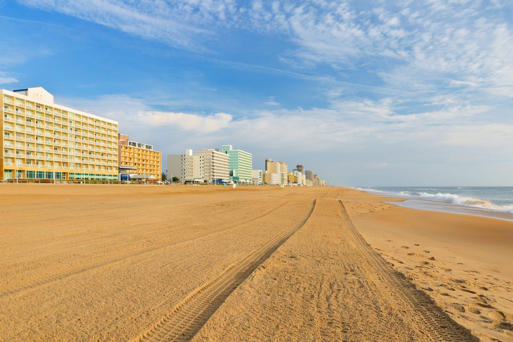 Virginia Beach in the early morning. A tyre trail stretches across the sand into the distance and hotels line the beachfront on the left.