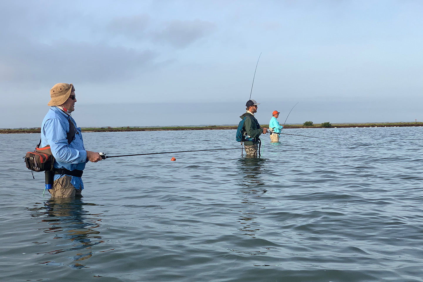 A group of anglers wade fishing in shallow sea water