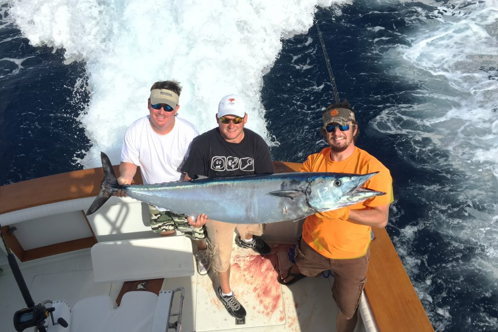 Three anglers with a big Wahoo caught offshore from Charleston