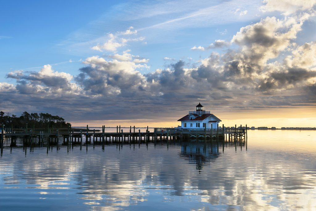 The harbor and lighthouse in the fishing town of Wanchese, North Carolina. The sun is rising out of the sea in the distance.