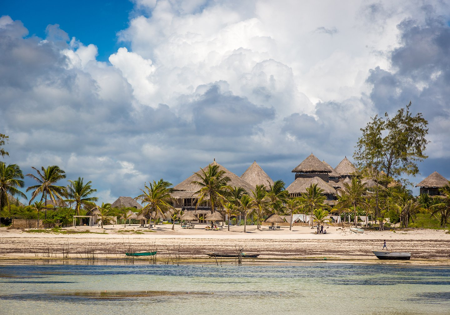 A view taken from the sea of traditional huts in Watamu, Kenya. There is shallow, clear water in the foreground and cloudy sky in the distance.