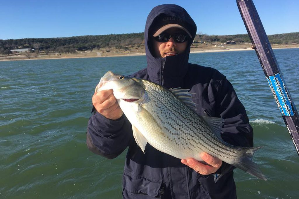 An angler in a black jacket holding a White Bass with water behind him
