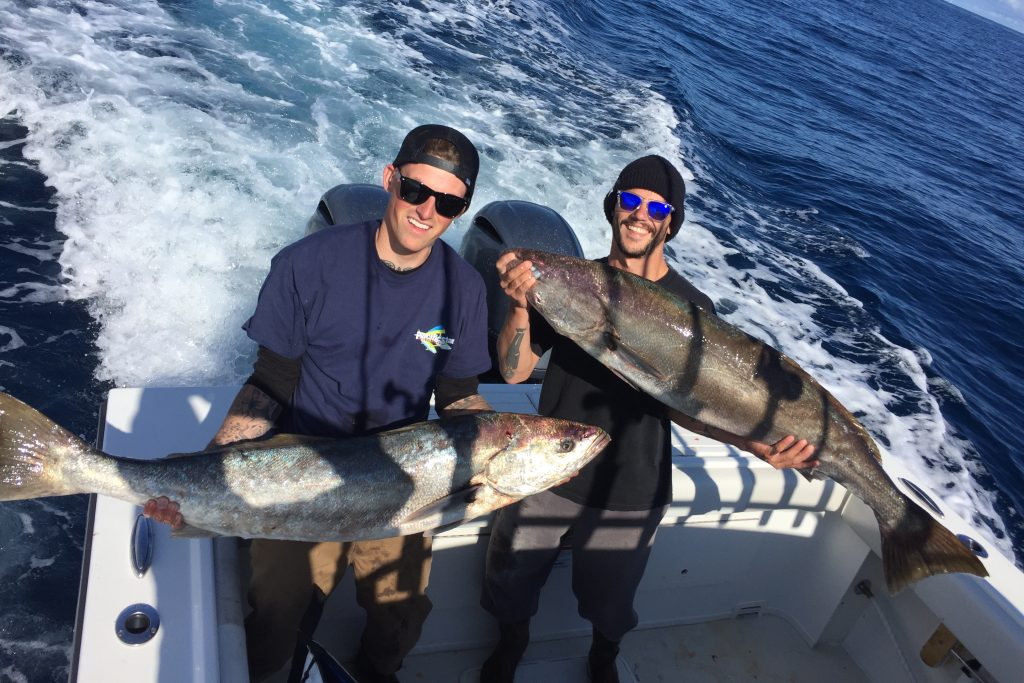 Two anglers holding big White Seabass on a fishing charter, with the boat's wake creating waves behind them