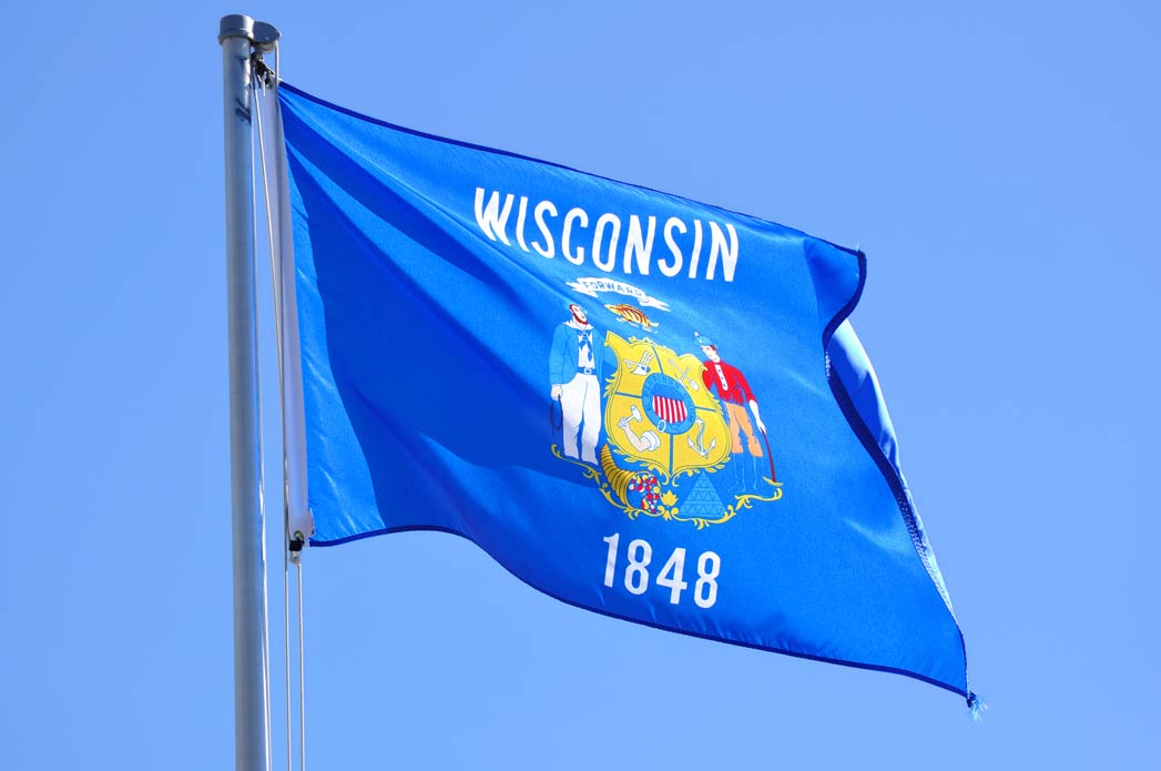 Images shows the Wisconsin State Flag against a blue sky