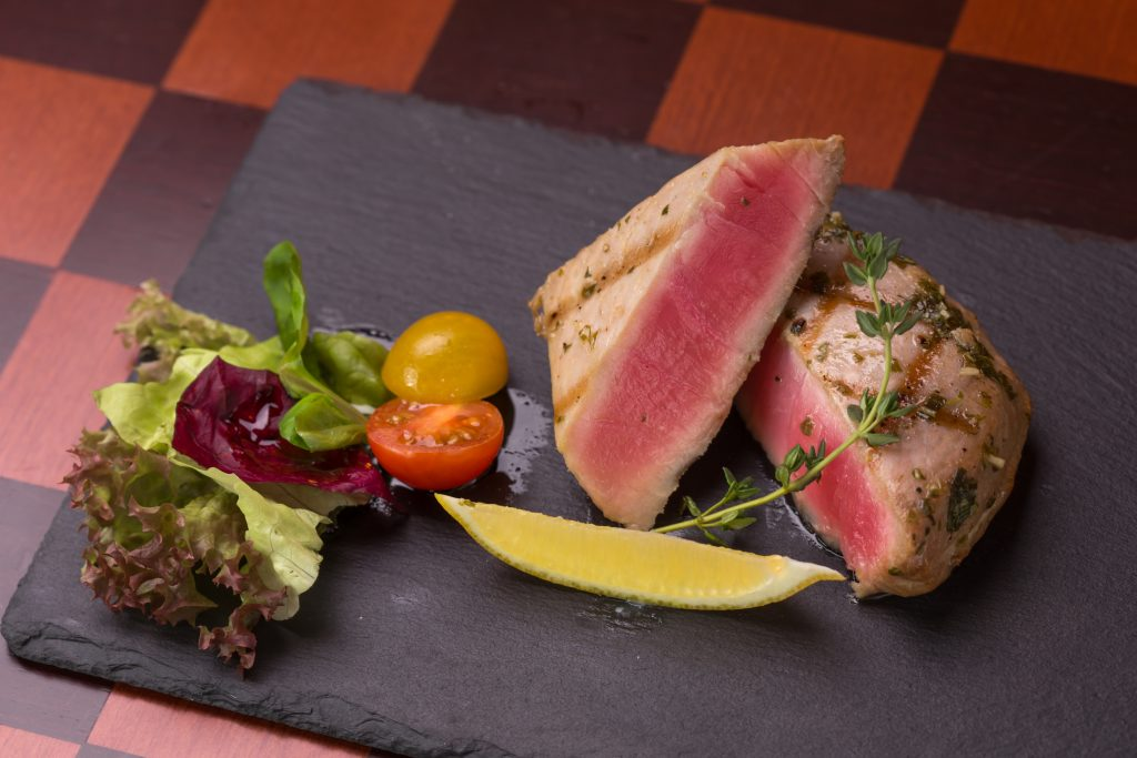 two Yellowfin Tuna steaks on a plate with a salad on the side