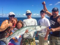 A family fishing in Florida and a boy angler holding a Barracuda