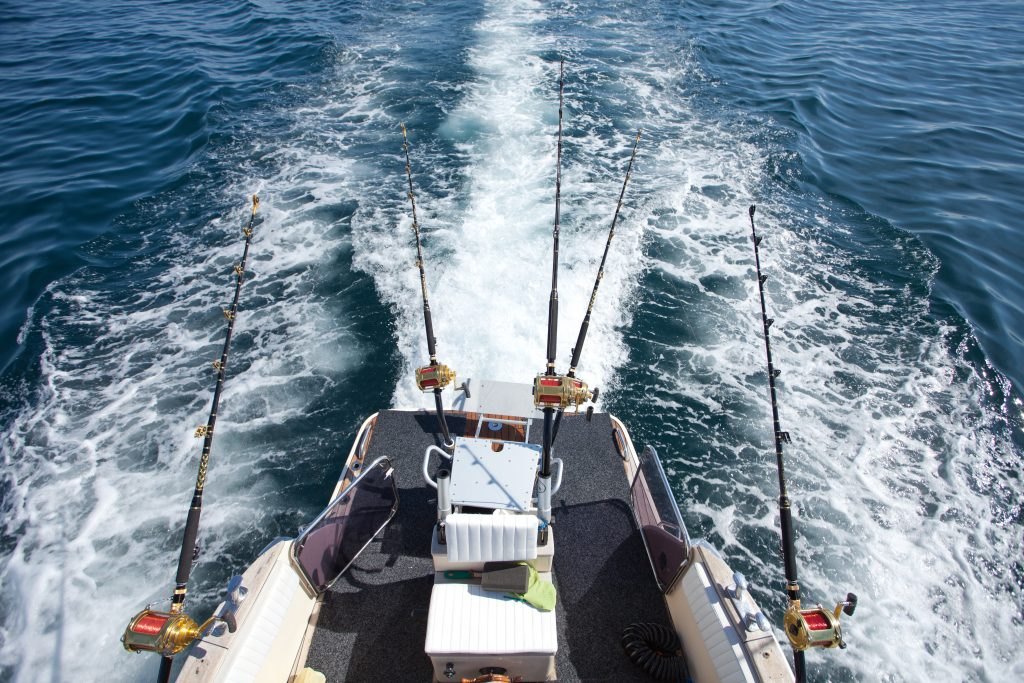 a bird's eye view of a moving trolling boat with lines in the water