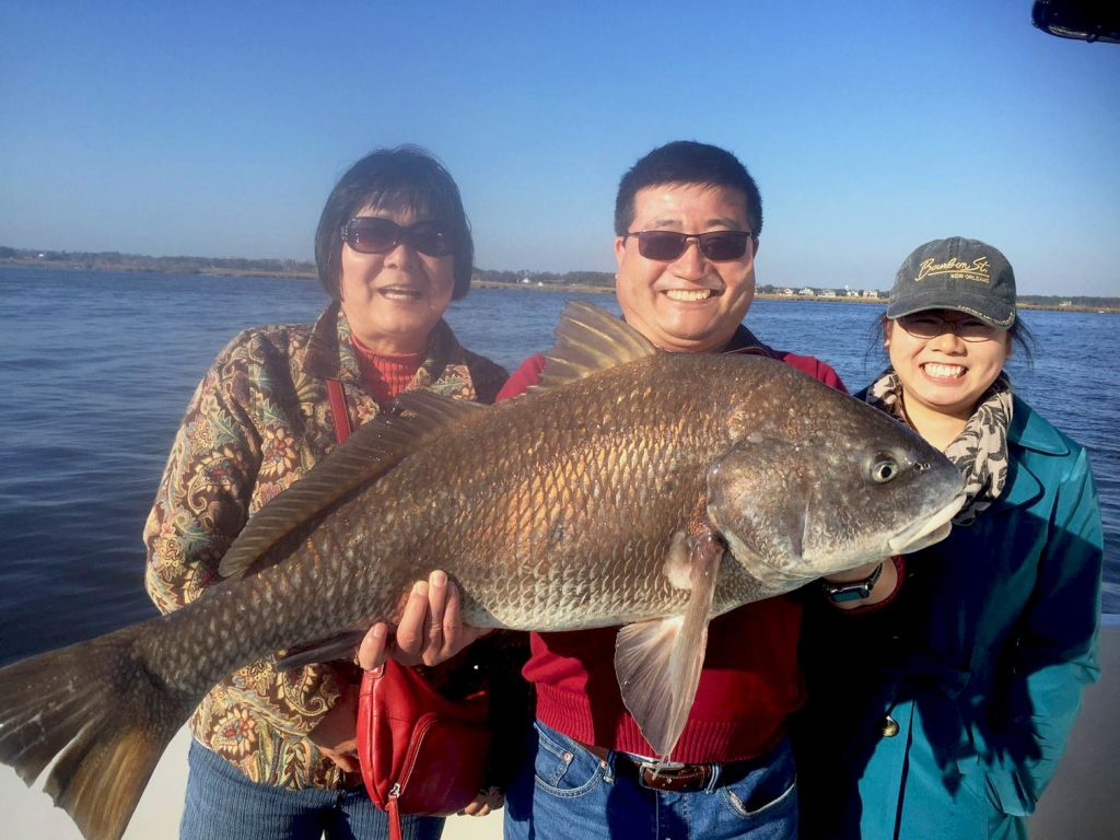A family smiling holding a big Black Drum