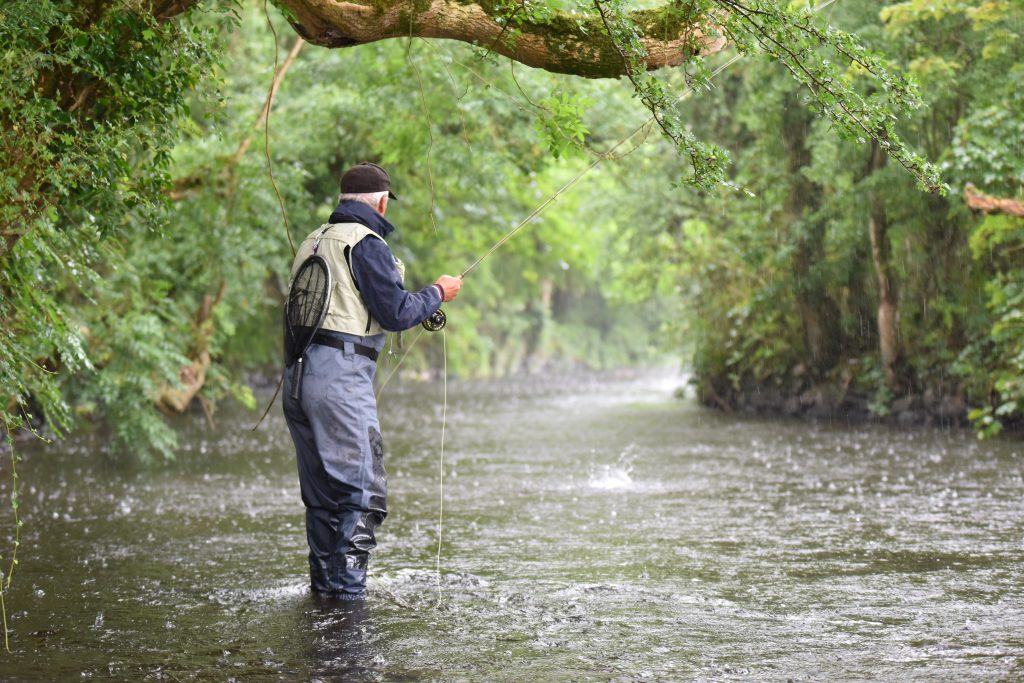 angler fly fishing in a river while it's raining