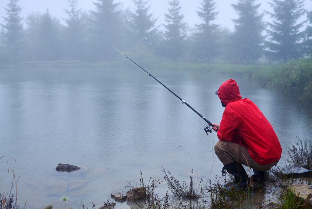 angler fishing a pond during bad weather