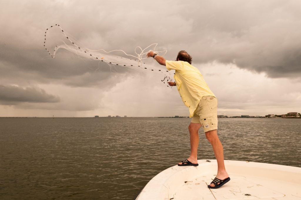 an angler casting a fishing net from a boat