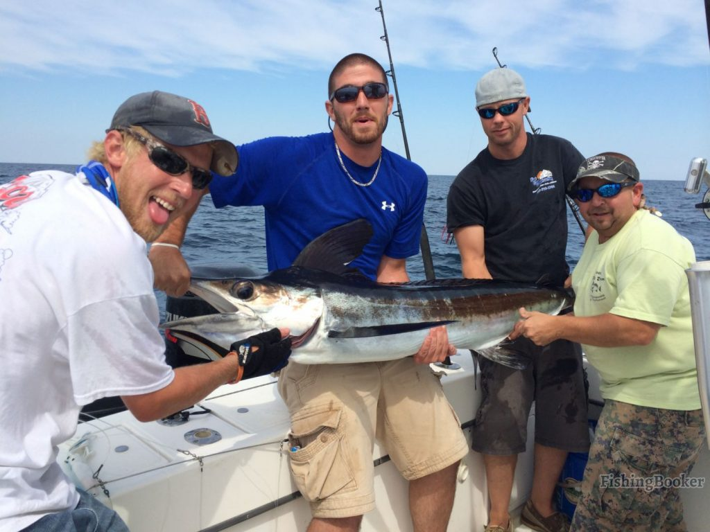 smiling anglers holding a Swordfish on a fishing boat