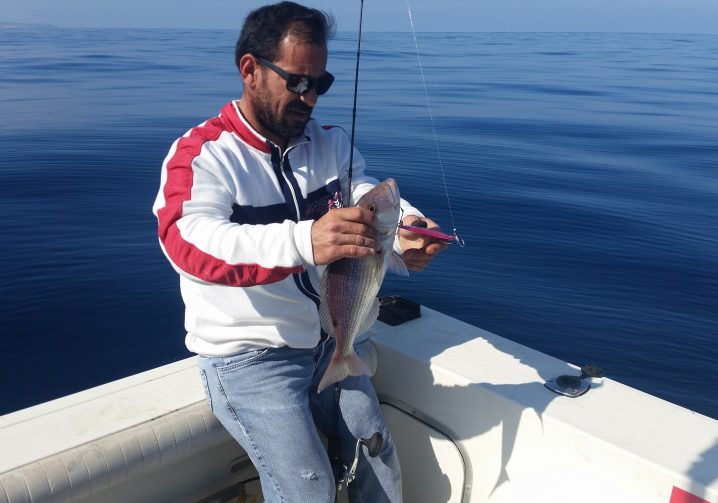 A man wearing jeans and a white and red jacket leaning on the side of a boat with ocean in the background. The man is holding a fish in one hand and a jigging lure in the other, with a fishing rod held between his legs.
