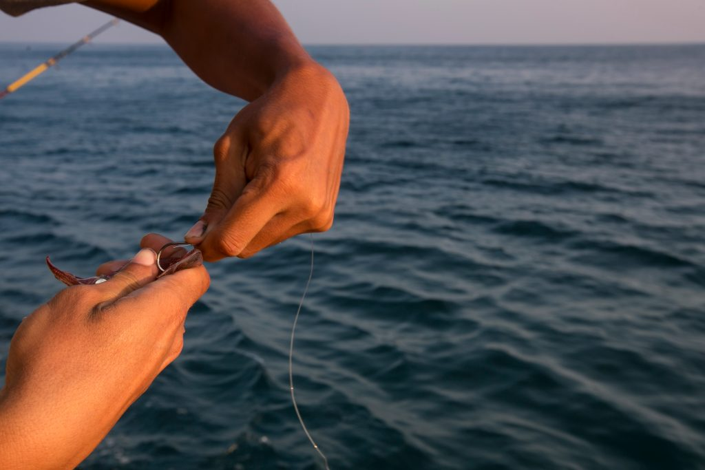 a close up of an angler baiting a fishing hook with live bait
