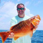 Belize bottom fishing: An angler holding a big Grouper