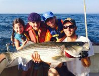 A family with young kids on their fishing trip holding a Striped Bass on boat out of Montauk.