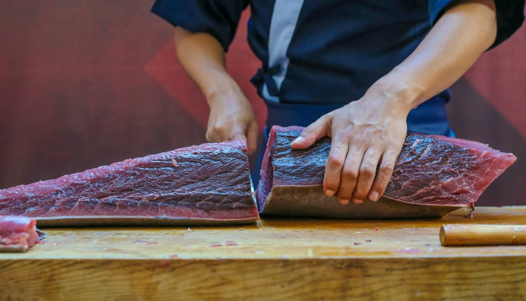 A chef cutting a large piece of bluefin tuna, the most expensive type of tuna in the world