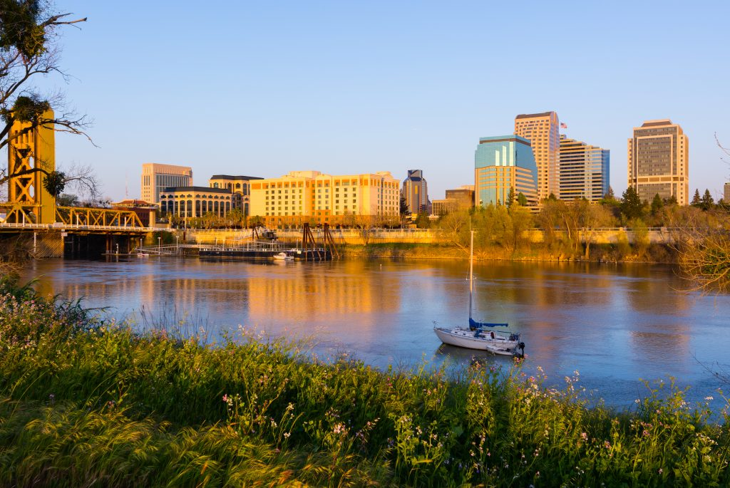 a boat on the sacramento river with the city skyline in the background
