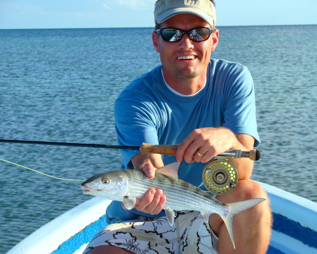A man sitting in a boat holding a Bonefish in one hand and a fly rod in the other.