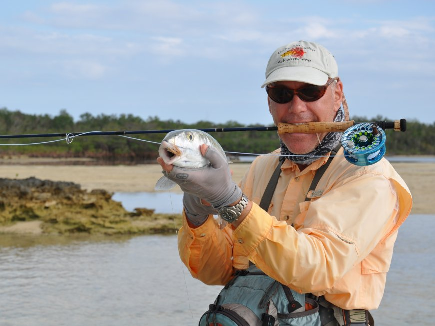 fly fisherman holding a fish