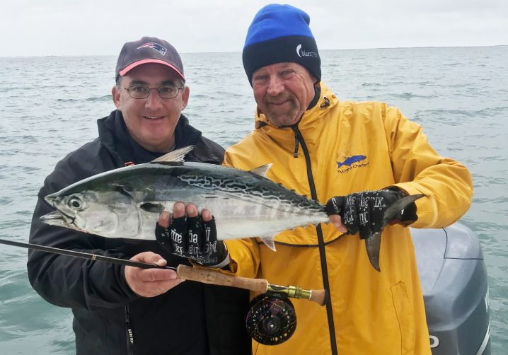 Two happy anglers holding a false albacore and a fly fishing rod with sea in the background.
