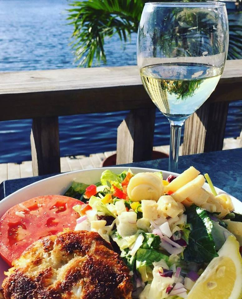 crab cake salad and a glass of white wine in coconut restaurant fort lauderdale