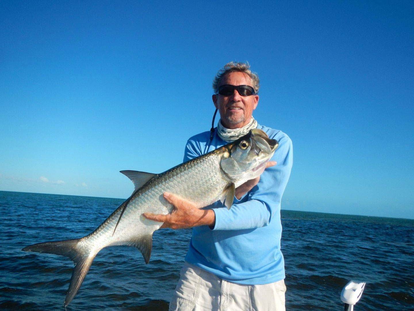 A man holding a Tarpon on a boat in the Florida Keys