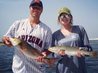 A couple holding a Redfish and a Speckled Trout which they caught in Destin Bay.