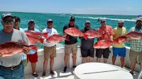 A group of anglers, each holding a Red Snapper they caught on a party boat from Destin, Fl