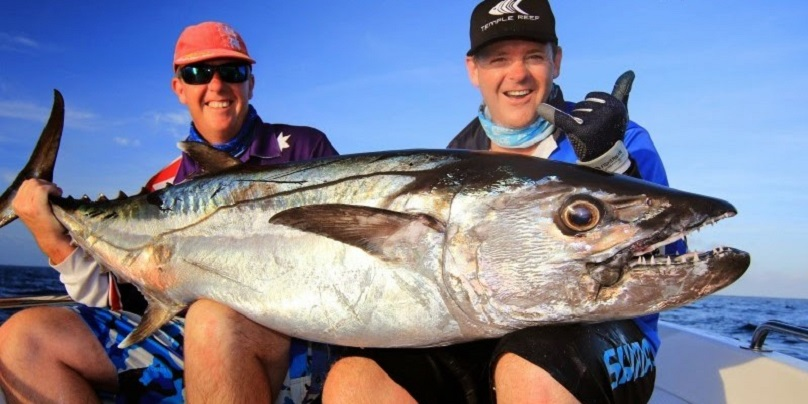 Two anglers holding a Dogtooth Tuna they caught while fishing in Port Moresby