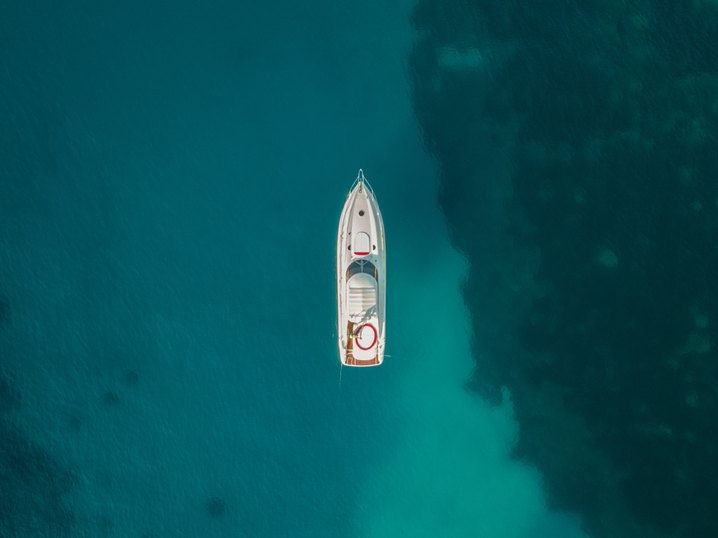 drone view of a boat near a water color break