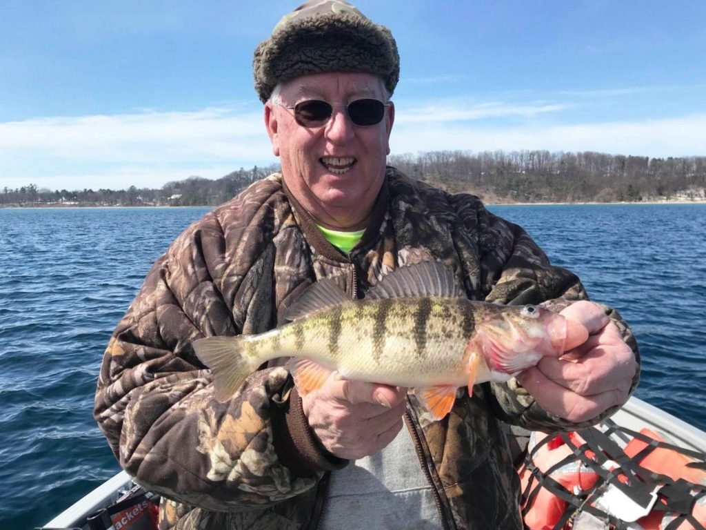 An angler holding a Yellow Perch on a boat