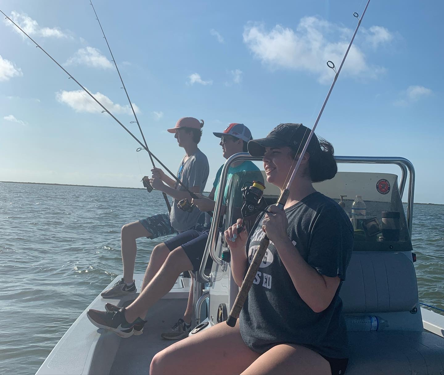 three teenage anglers casting rods on a fishing boat