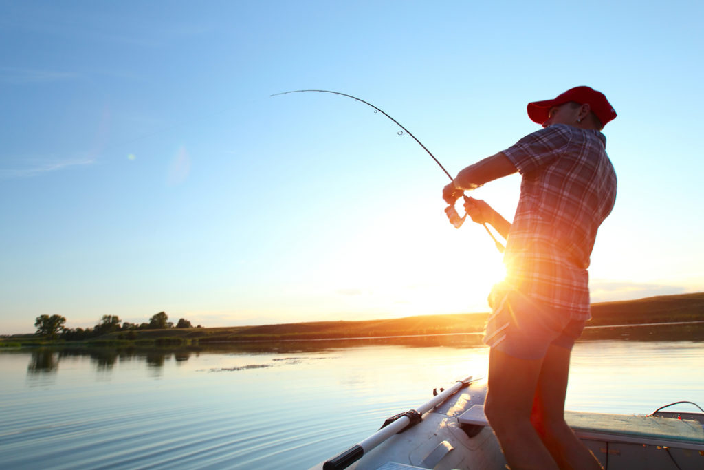 an angler fishing from a boat with the sun rising in the background