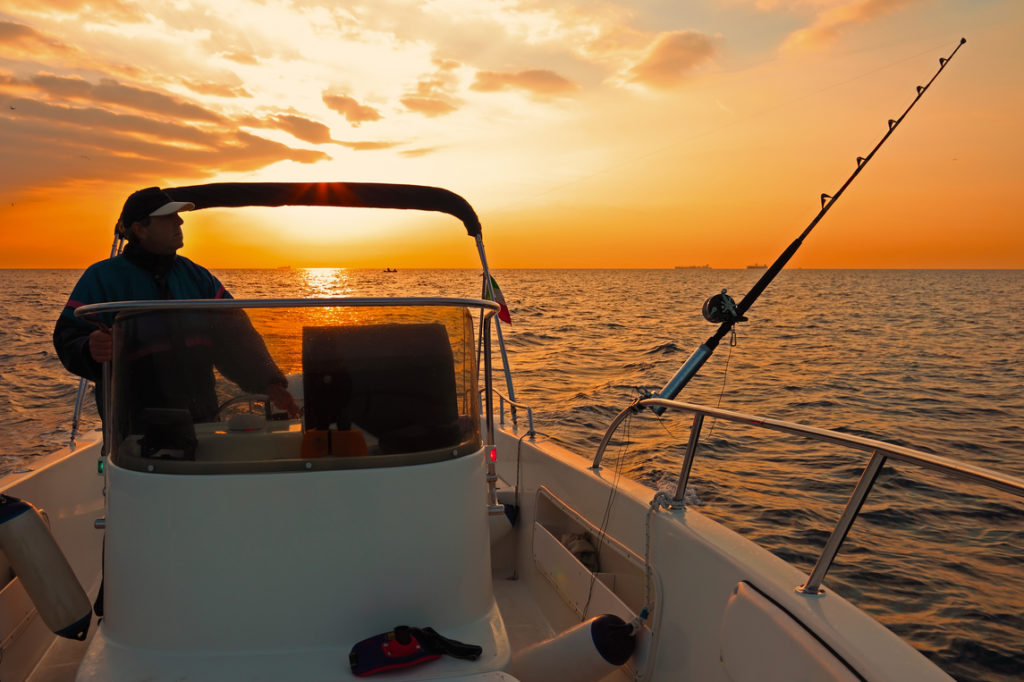 an angler on a fishing boat at dawn, one of the best times to go fishing, especially in the summer